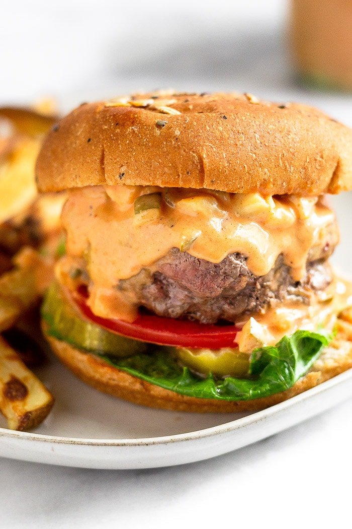 Hamburger with lettuce, tomato, and pickles topped with burger sauce that is dripping down the burger.