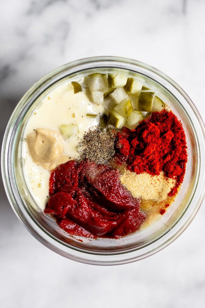 Jar filled with homemade mayo, tomato paste, mustard, chopped pickles, and spices to make special sauce.