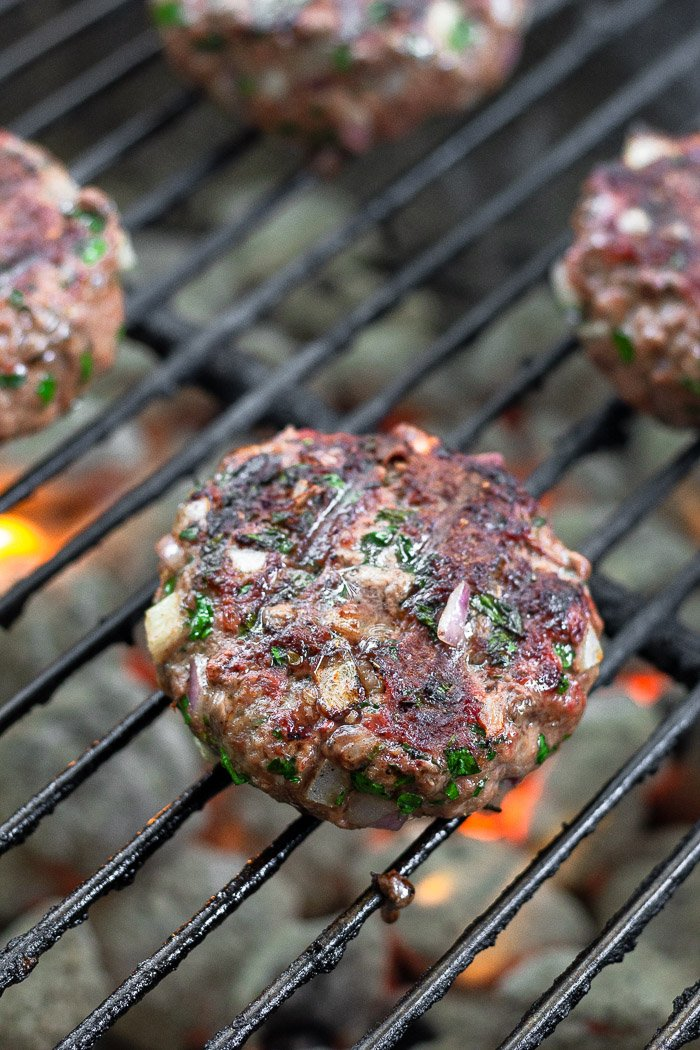 Grilled greek burgers on charcoal grill.