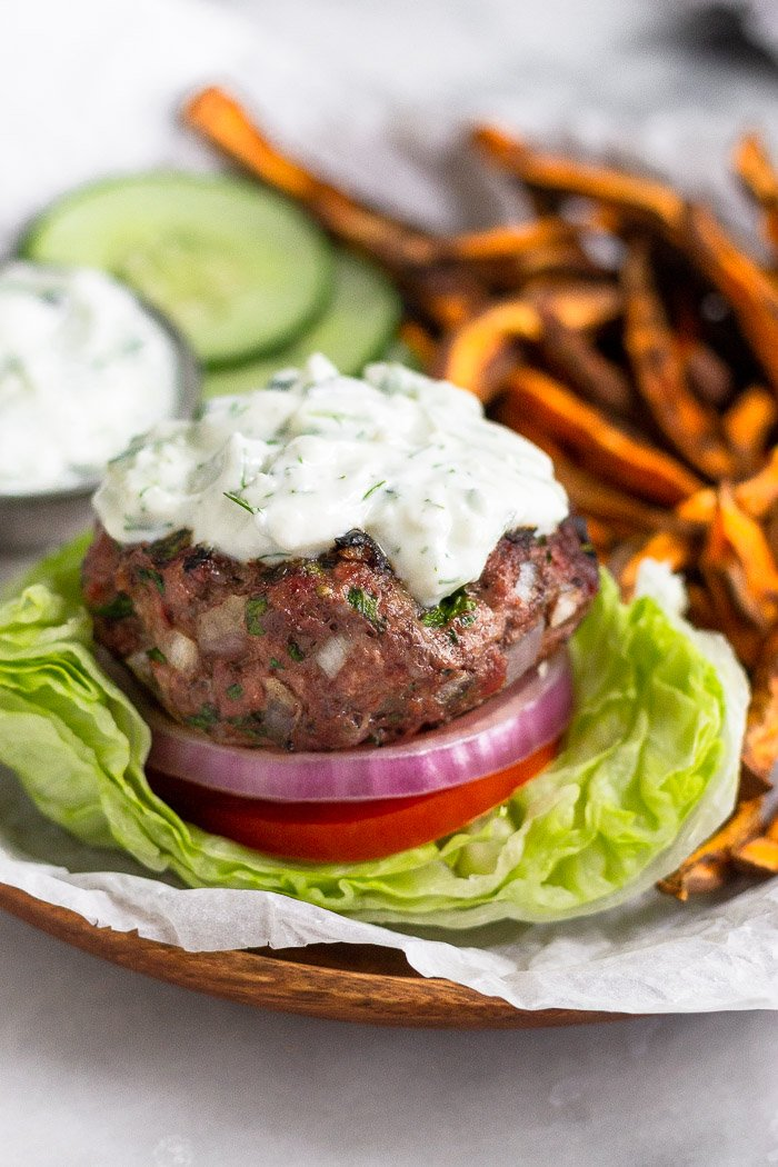 Greek lamb burger on a plate. It is sitting in a lettuce wrap with tomato, onion, and topped with tzatziki sauce. Behind it is sweet potato fries, sliced cucumbers, and a dish of tzatziki sauce.