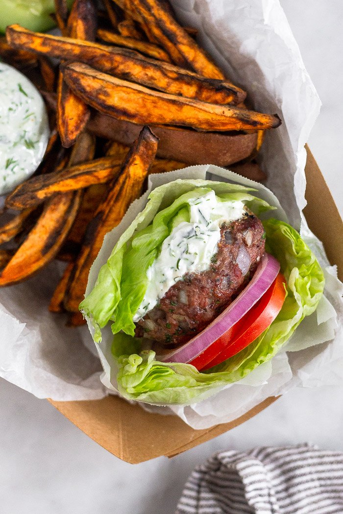 Overhead shot of a basket filled with a lettuce wrapped mediterranean burger with tzatziki sauce, sweet potato fries, and a small dish of tzatziki.