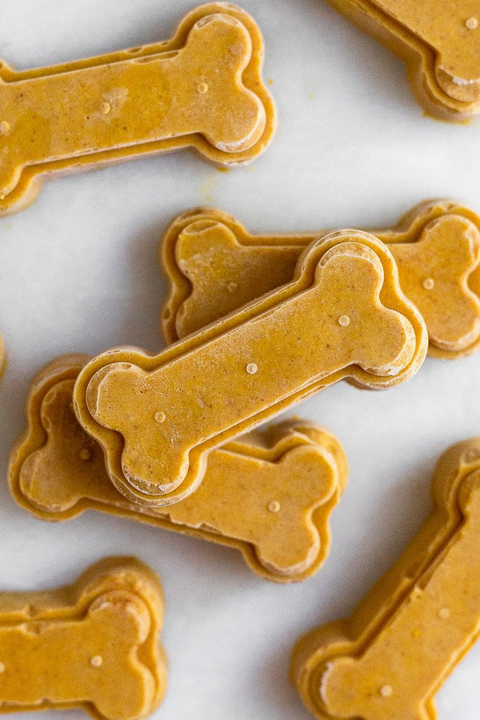 Frozen pumpkin peanut butter dog treats spread out on a white counter top with some stacked on top of each other.