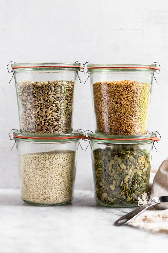 Four large glass jars, two stacked on top of each other. They are filled with sunflower seeds, flax seeds, pumpkin seeds, and sesame seeds for seed cycling.