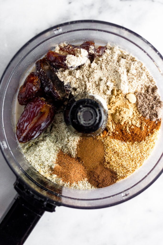 Overhead shot of a food processor filled with sound seeds, dates, protein powder, spices, and almond milk.