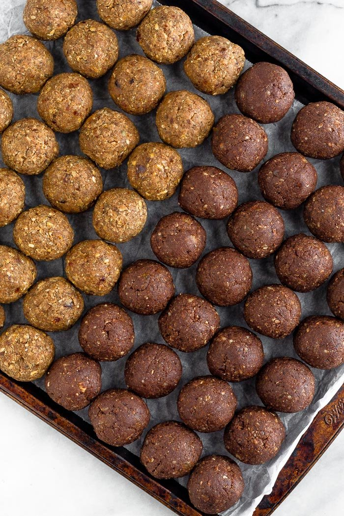 Cookie sheet lined with parchment paper with two kinds of Seed cycling date balls