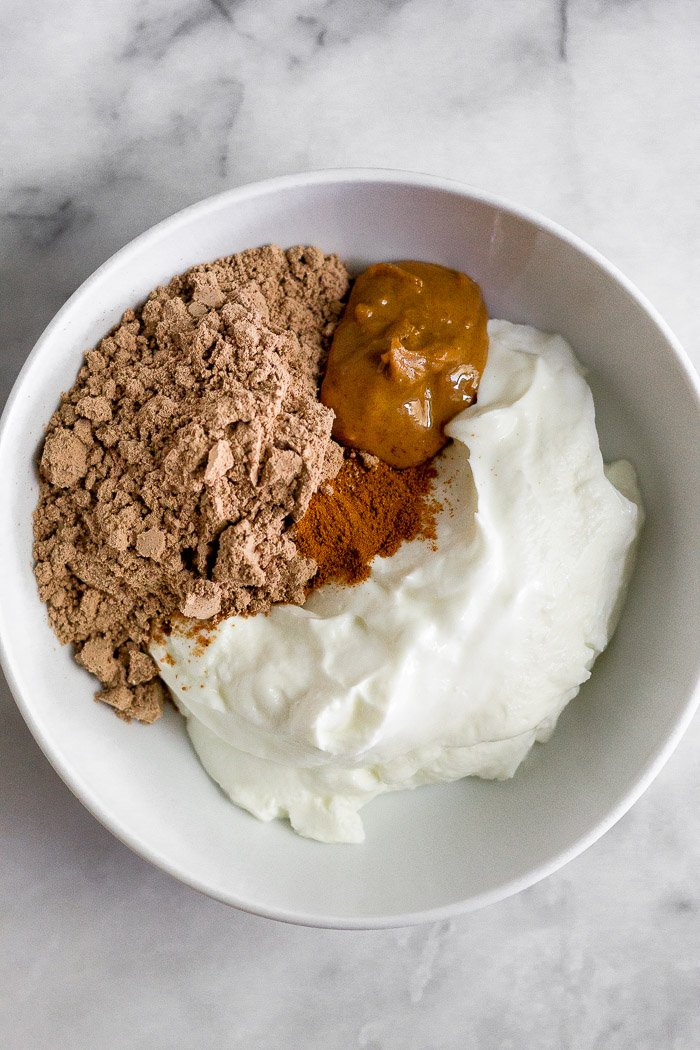 White bowl filled with yogurt, chocolate protein powder, peanut butter, and cinnamon
