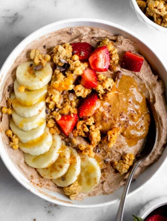 Protein yogurt bowl topped banana, granola, strawberries, peanut butter, and honey. A spoon is coming out of the bowl.