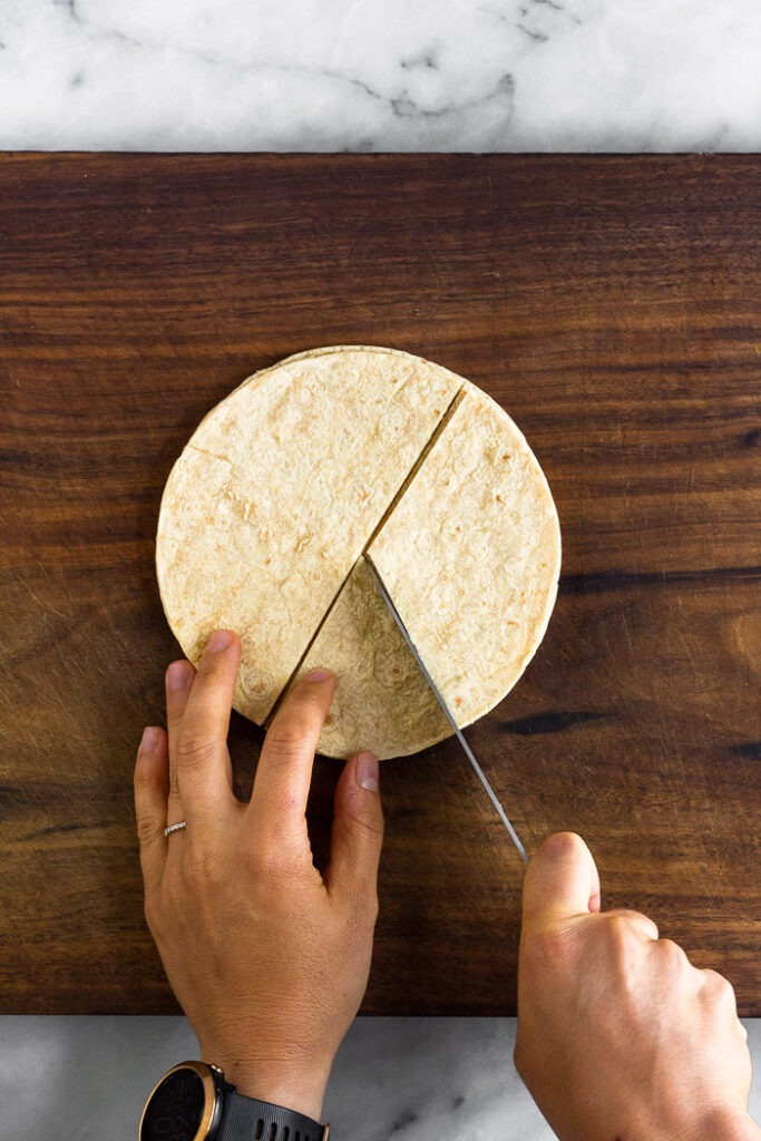Overhead shot of corn tortillas being cut.