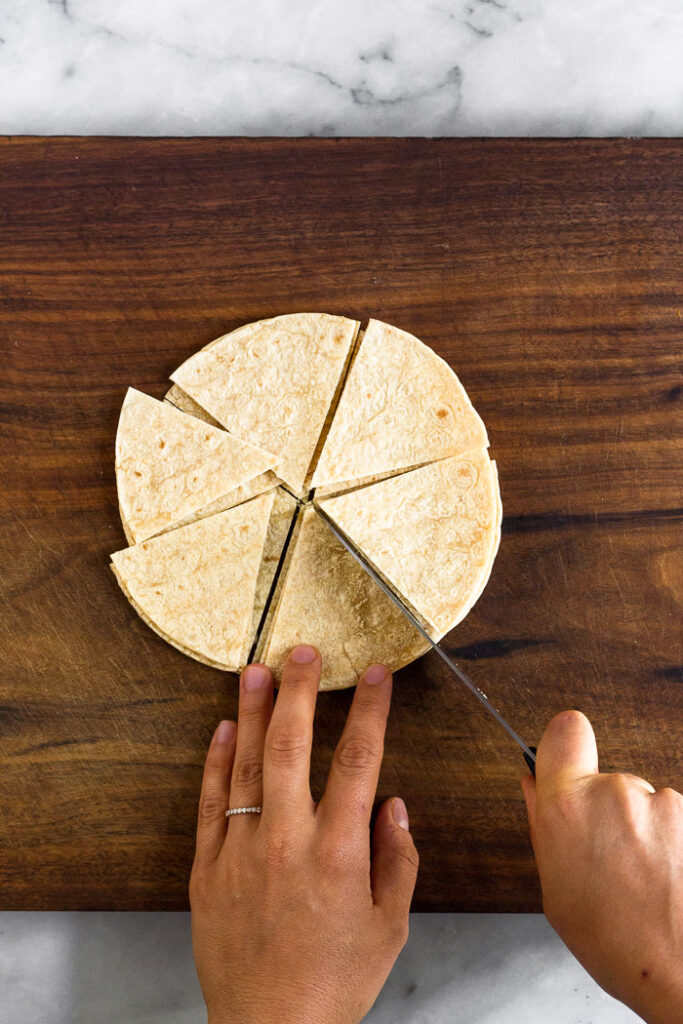 Overhead shot of corn tortillas being cup into triangles.