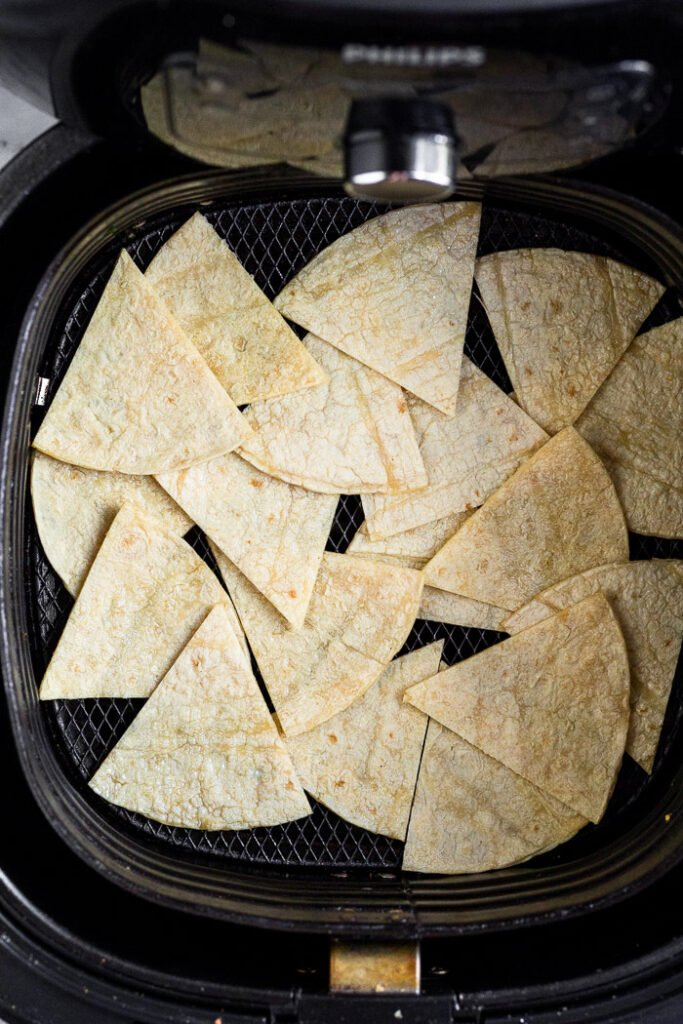 Cut up corn tortillas in an air fryer basket.
