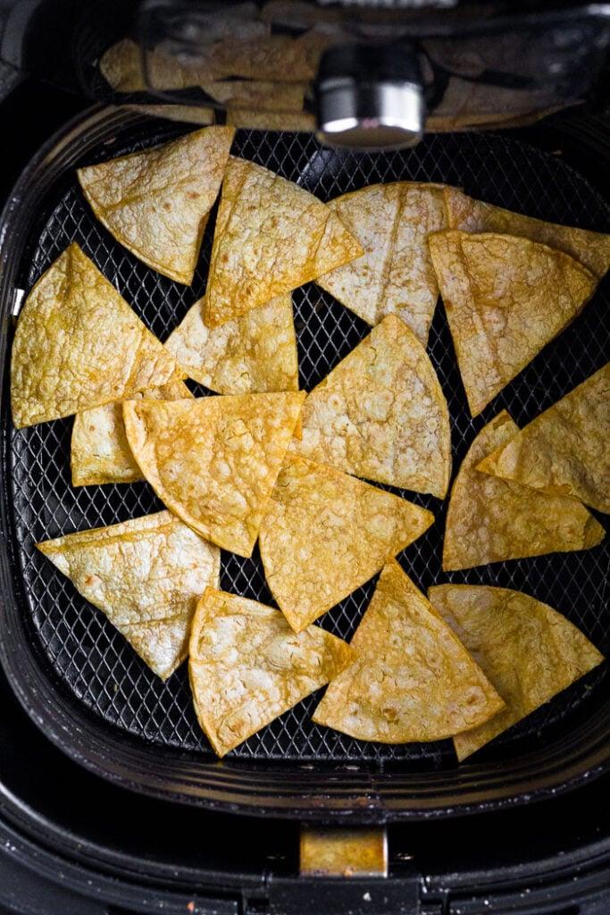 Homemade corn tortilla chips in an air fryer basket.