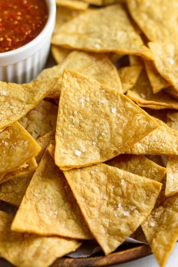 Close up of homemade tortilla chips with salt. In the background is a container of salsa.