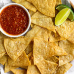 Overhead shot of a plate of air fryer tortilla chips with a small bowl of salsa and 2 lime wedges.