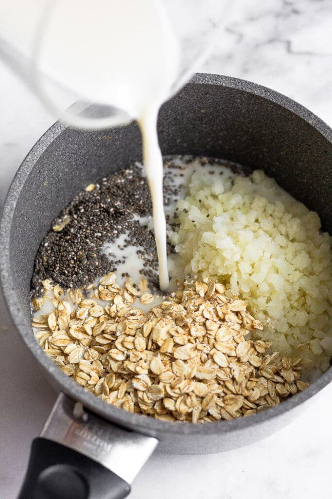 Saucepan with rolled oats, riced cauliflower, and chia seeds with milk bring poured in into it.