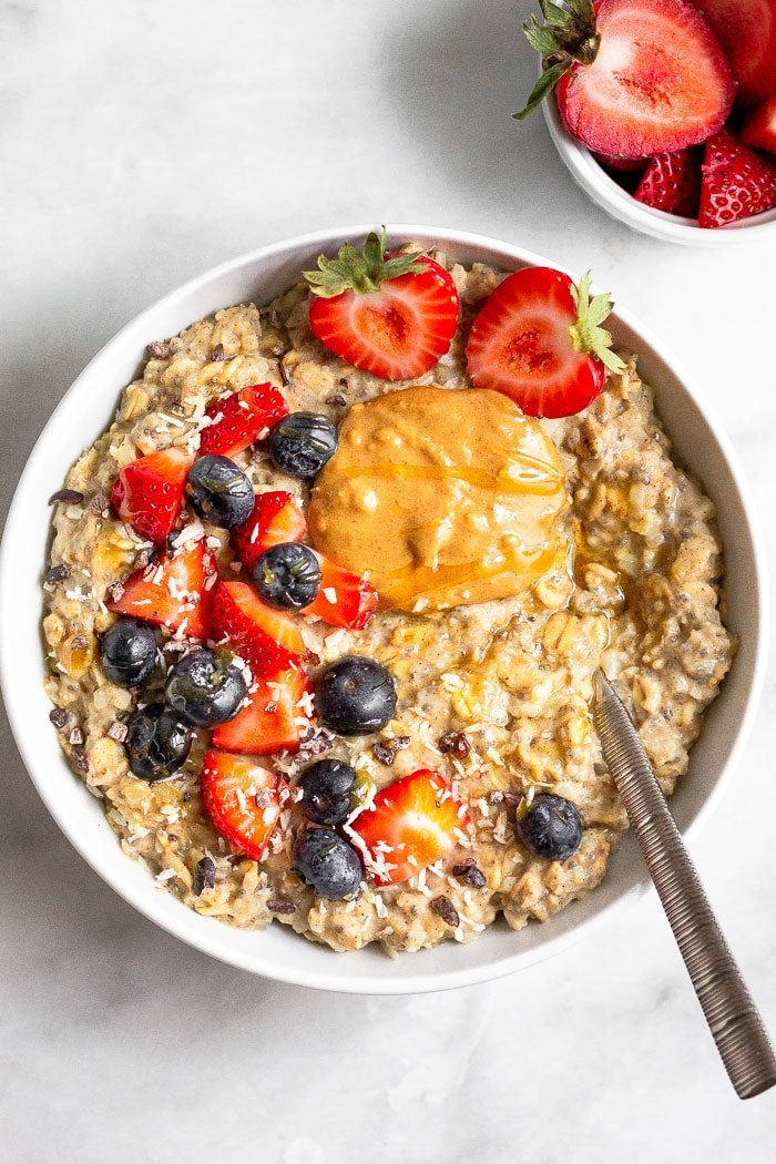 Overhead shot of riced cauliflower oatmeal topped with berries, peanut butter, and honey. A spoon is in the bowl and a small bowl of chopped strawberries is next to the bowl.