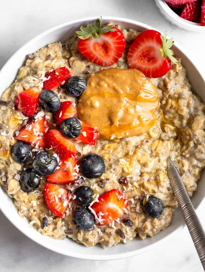 Bowl of cauliflower oatmeal topped with berries and peanut butter with a spoon coming out of it. There is a small bowl of cut up strawberries next to it.