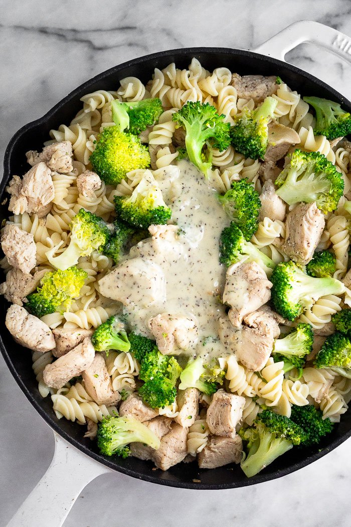 Overhead shot of a pan filled with chicken broccoli pasta with ranch dressing poured on top.
