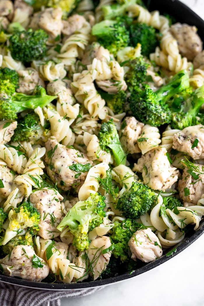 Close up of broccoli chicken pasta in a large pan with lots of fresh herbs mixed in.