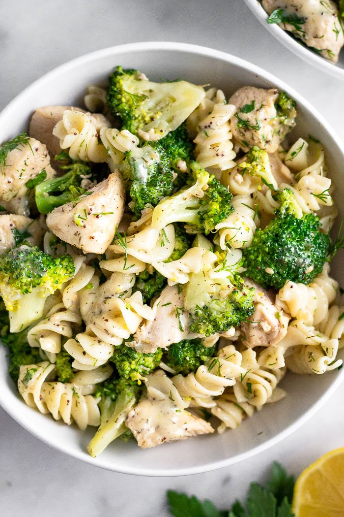 Bowl of chicken and broccoli pasta with ranch dressing. Next to is is another bowl, half a lemon, and some parsley.