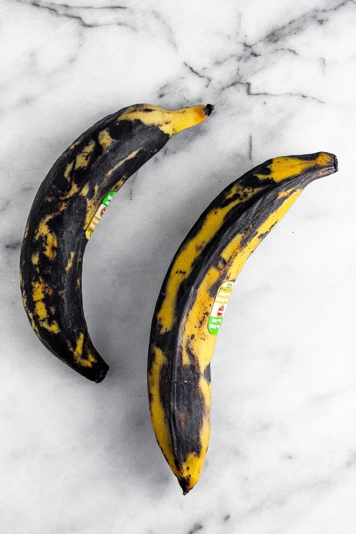 Two ripe plantain that are mostly brown with a little yellow in them.