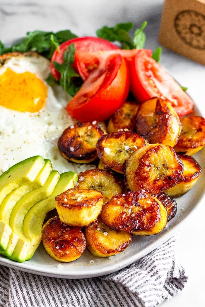 Plate of fried plantains, avocado, eggs, and tomatoes on top of a striped towel.