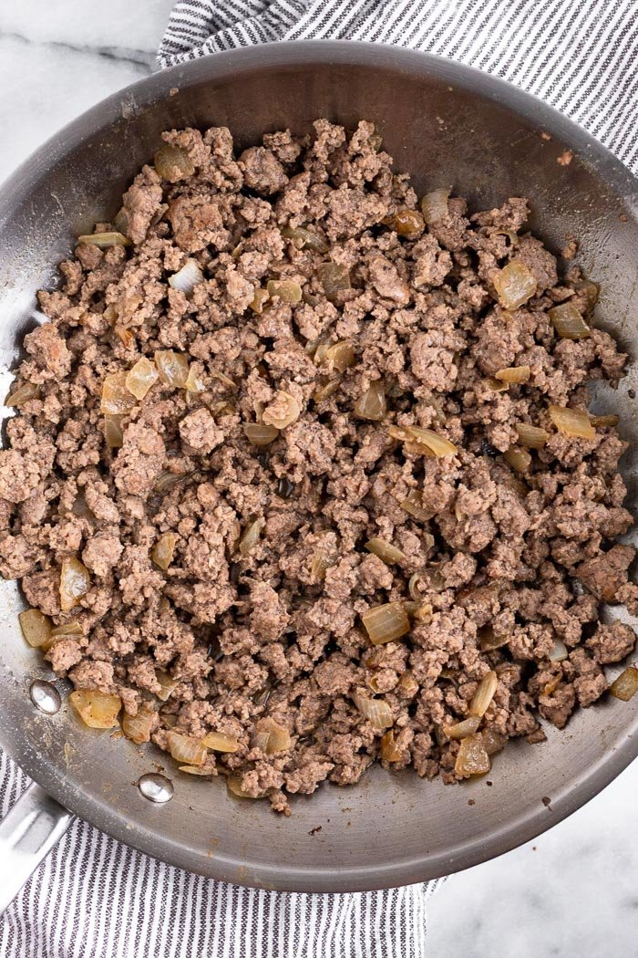 A pan filled with cooked ground beef and onions.