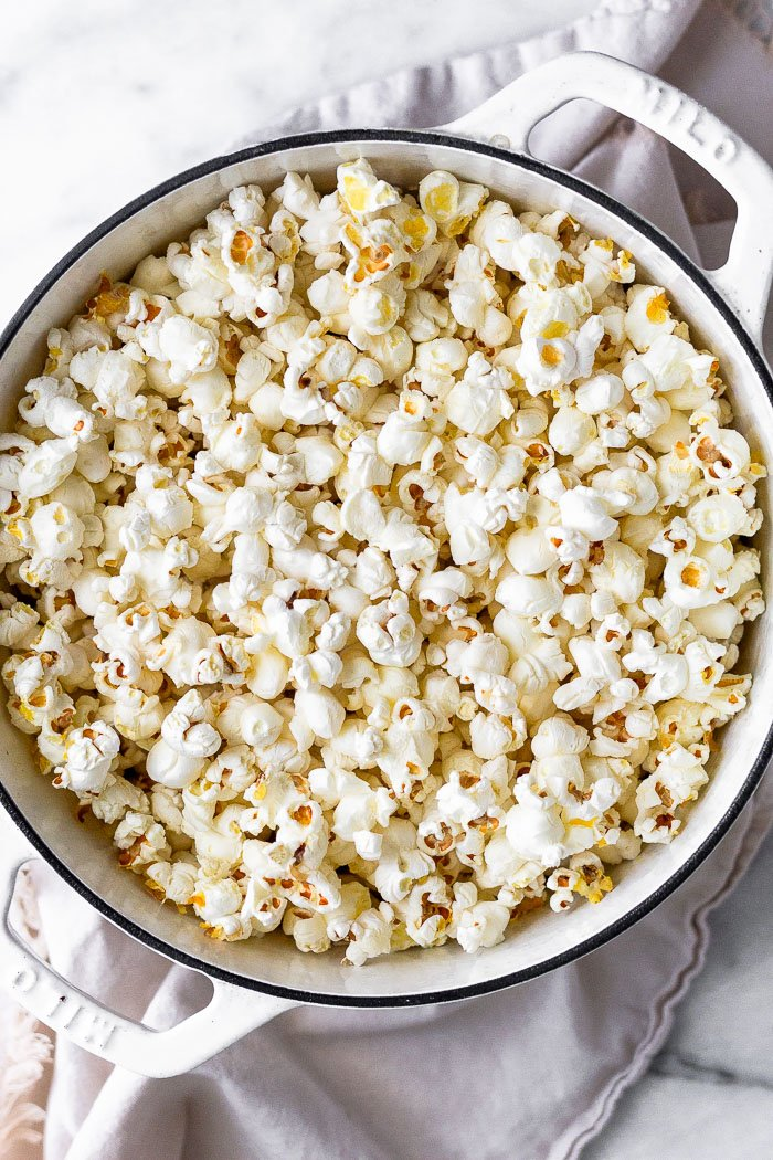 Large dutch oven filled with freshly popped popcorn in it.