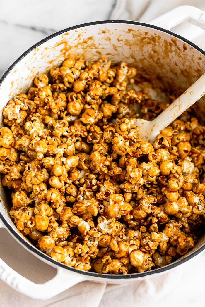 Large dutch oven with popcorn being mixed with caramel sauce without corn syrup.