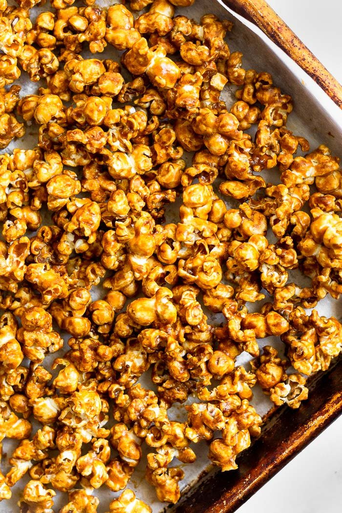 Overhead shot of a baking sheet filled with homemade caramel popcorn without corn syrup.