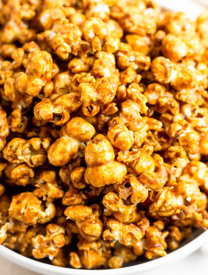 A close up of a white bowl filled with homemade caramel popcorn.