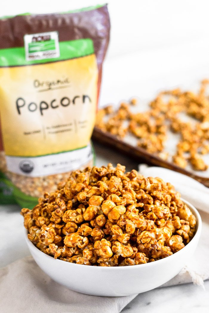 A bowl of homemade caramel corn with a bag of popcorn and a baking sheet with more caramel corn behind it.