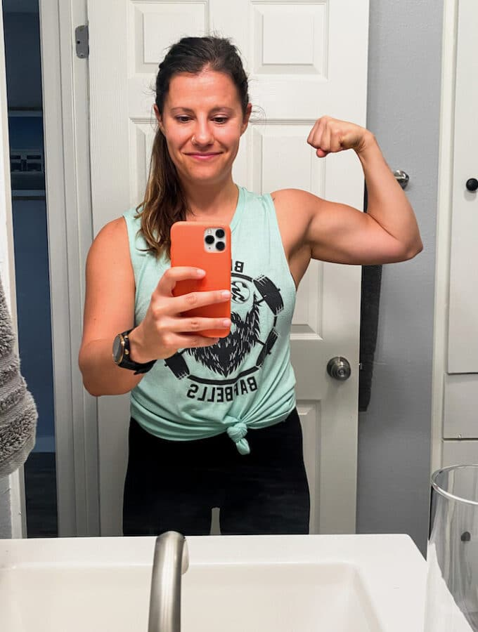 Girl in the mirror taking a selfie and flexing