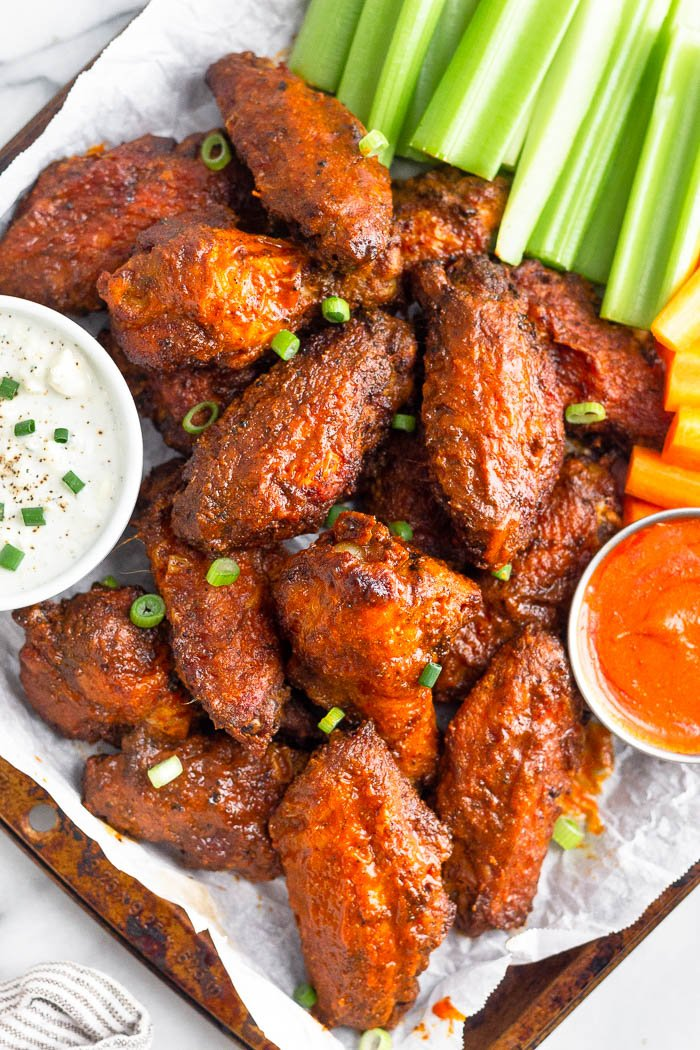 A tray of air fryer wings with blue cheese, hot sauce, celery, and carrots next to them.