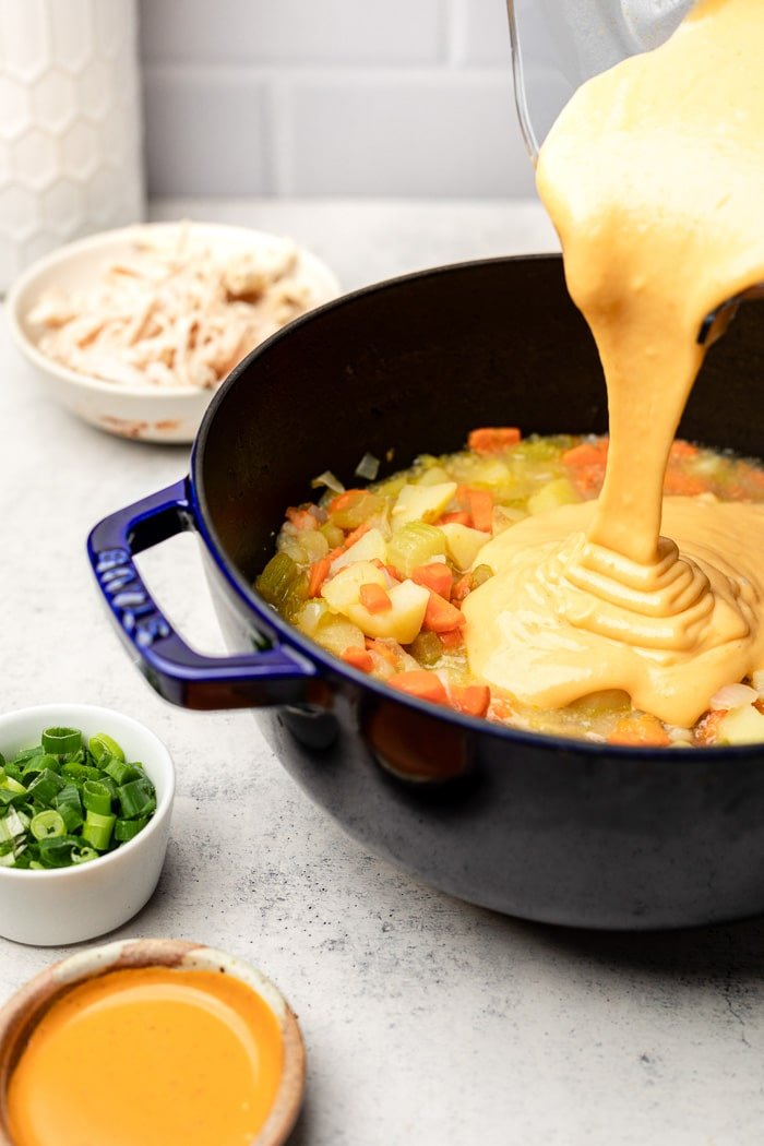A pot of paleo chicken soup with a thick broth being poured into it. Around it is a bowl of hot sauce. a bowl of green onions, and a bowl of shredded chicken.