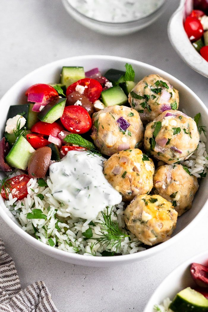 Greek bowls with greek meatballs, rice, greek salad, and Tzatziki. Behind it is another bowl with greek salad and a small bowl with tzatziki.