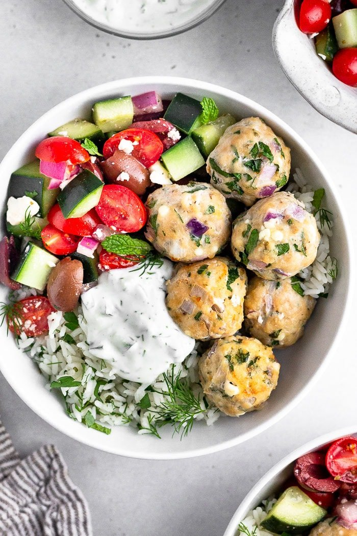 Mediterranean meatballs in a bowl with rice, greek salad, and tzatziki. Around it is more bowls with greek salad, a small bowl with tzatziki, and a kitchen towel.