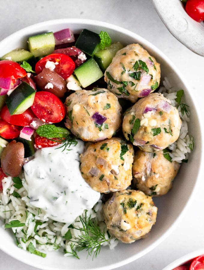 Bowl of greek chicken meatballs with rice, greek salad, and tzatziki sauce.