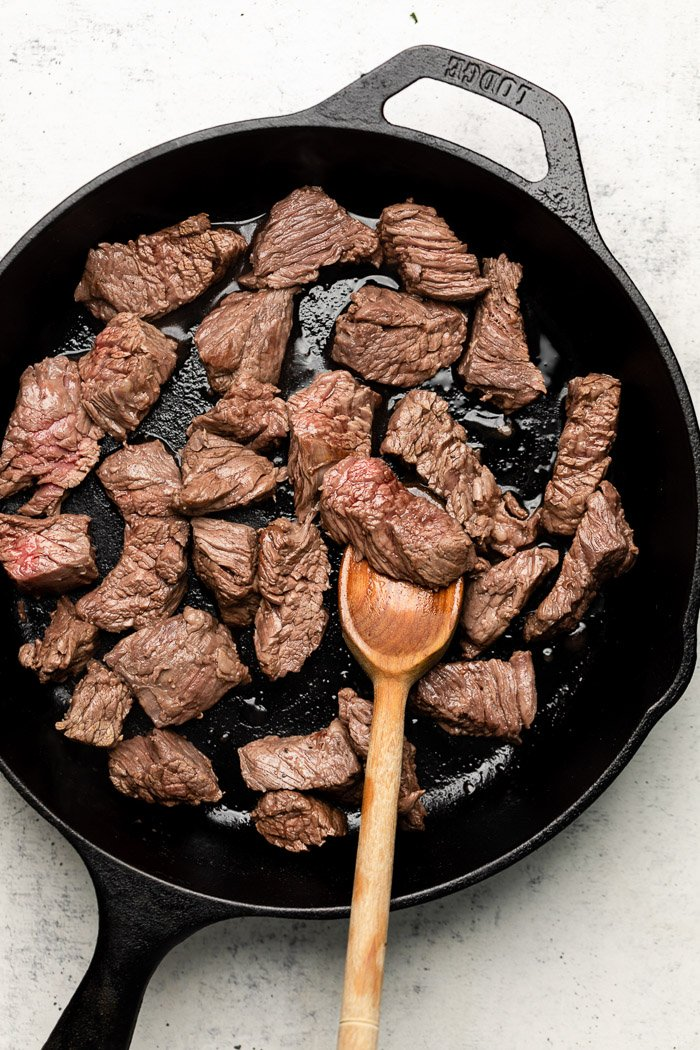 Pan filled with steak bites with a wooden spoon.