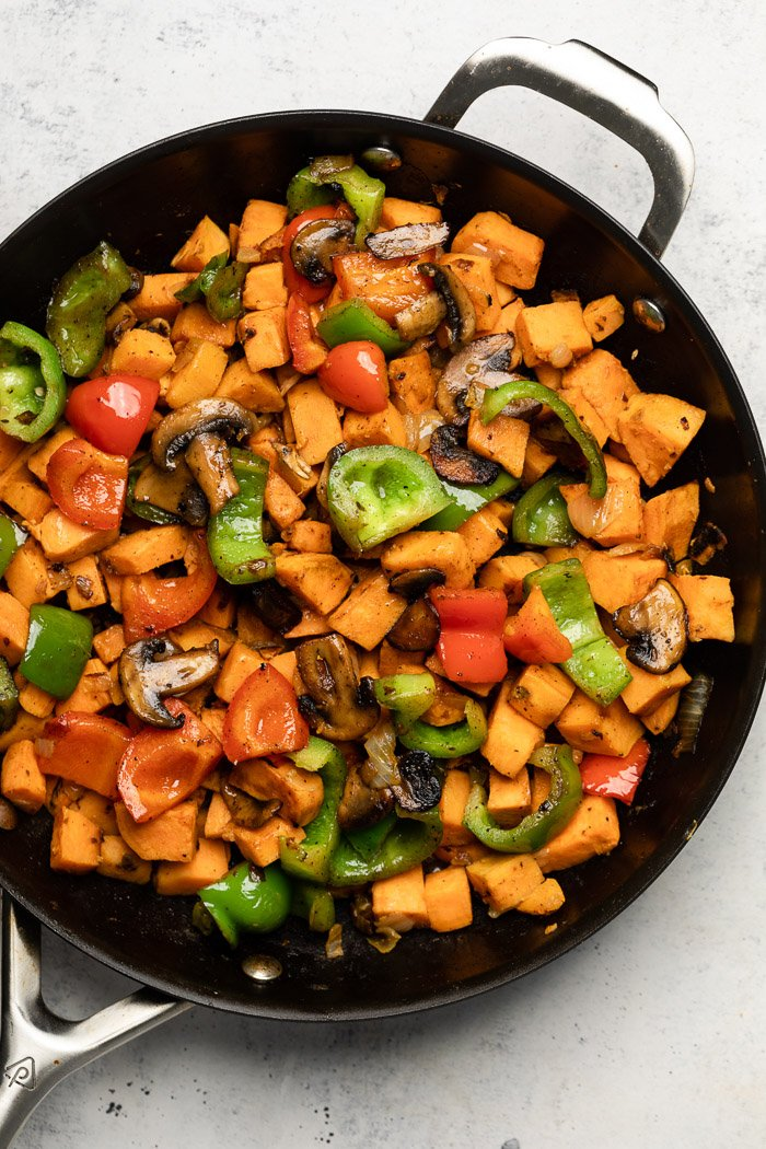 Large pan filled with diced sweet potatoes, peppers, and mushrooms.