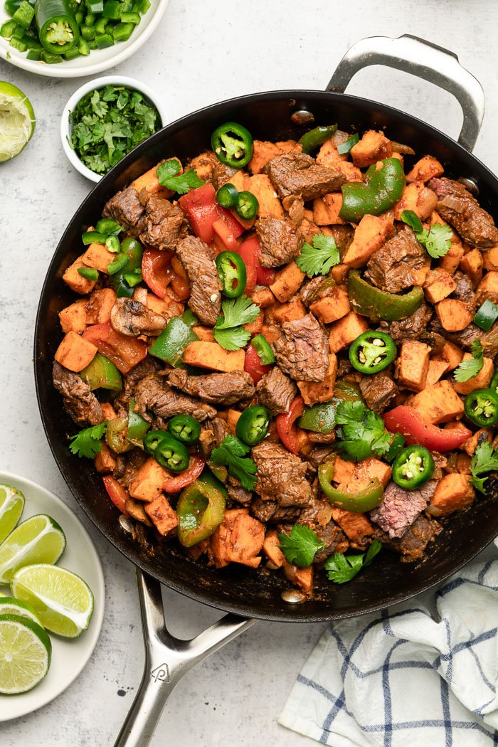 Steak and sweet potato skillet in a large pan topped with jalapeños and cilantro. Around it is a towel, lime wedges, and cilantro.