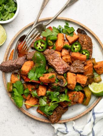 Plate with steak and sweet potato topped with cilantro and jalapeños. Next to it is a stripped towel, lime wedge, and a bowl of cilantro.