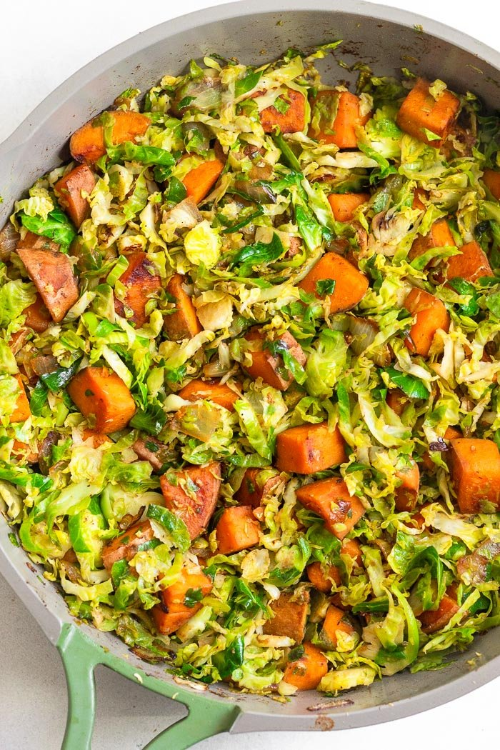 Skillet filled with cooked sweet potatoes and shredded Brussel sprouts.