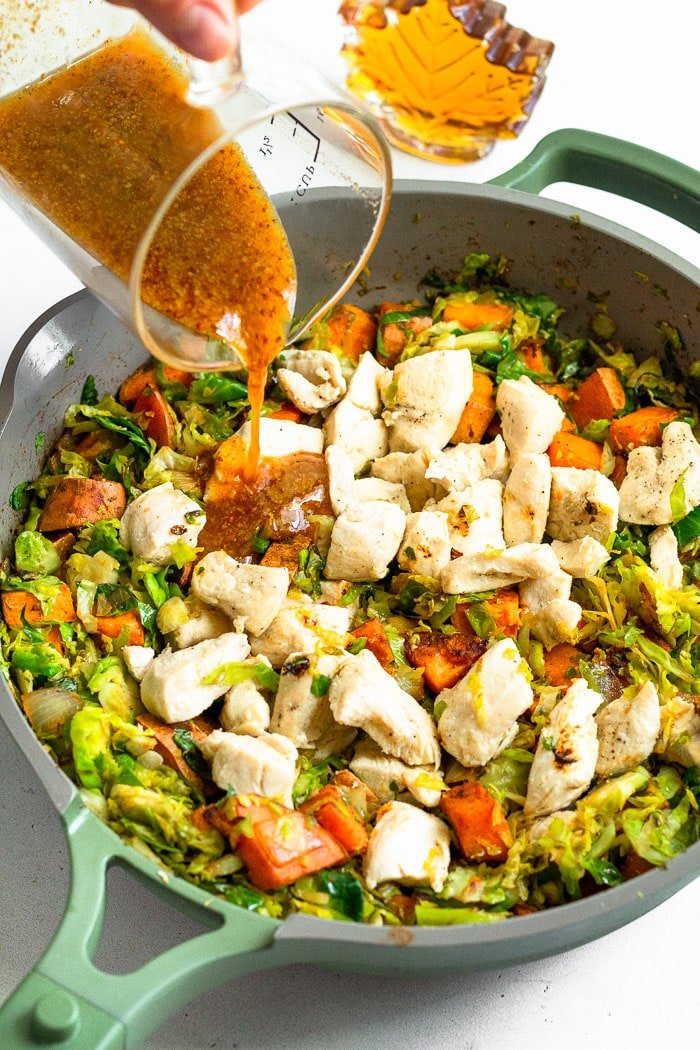 Skillet filled with sweet potatoes, shredded Brussel sprouts, and chicken with a maple mustard sauce being poured over top.