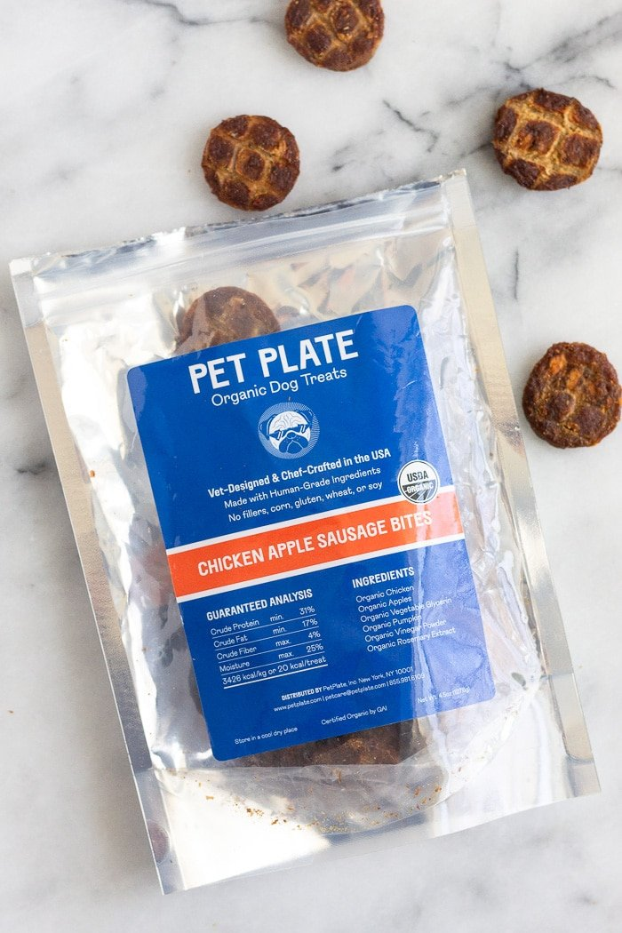 A bag of Pet Plate treats with some treats around it on a marble countertop.