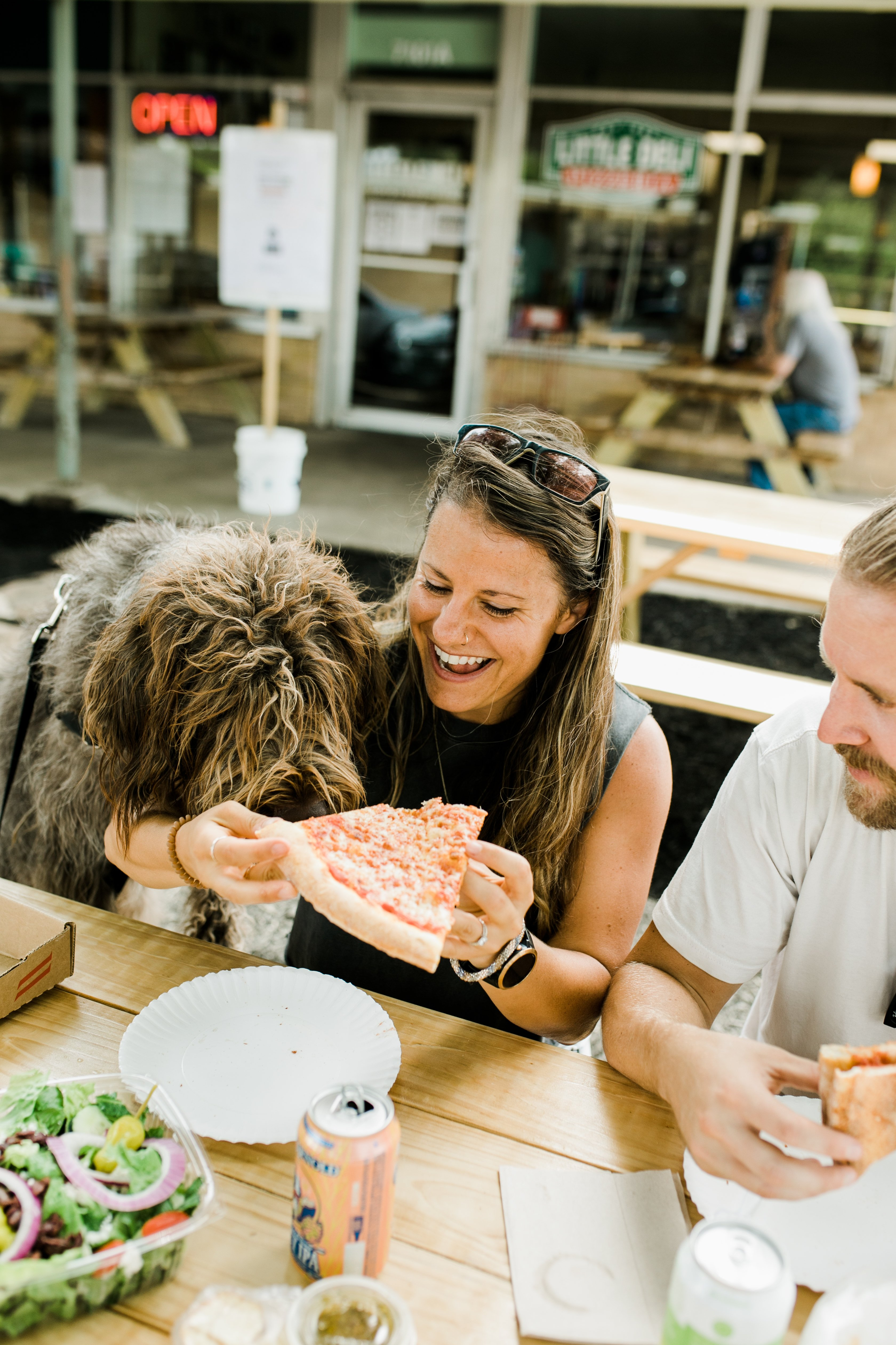 Female nutrition coach eating pizza with her dog and husband outside at a picnic table. She has a huge smile on her face.