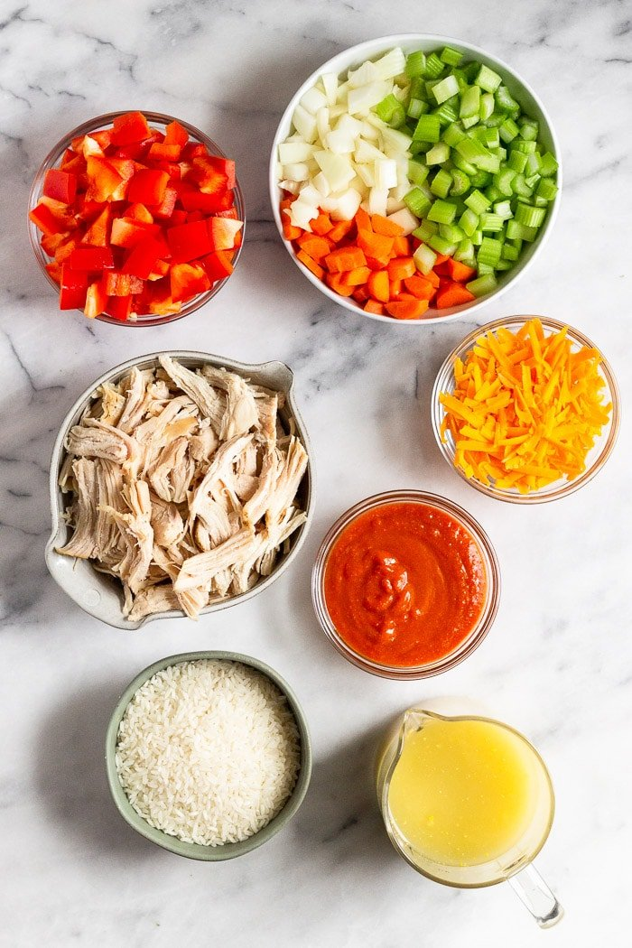 Overhead shot of a bowl of chopped veggies, bowl of shredded cheese, bowl of hot sauce, cup of broth, bowl of rice, bowl of shredded chicken, and a bowl of diced peppers.