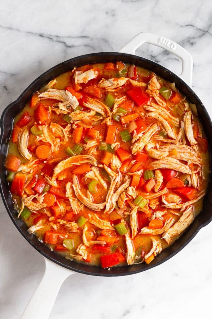 Large cast iron filled with sautéed veggies, shredded chicken, and a buffalo broth mixture.