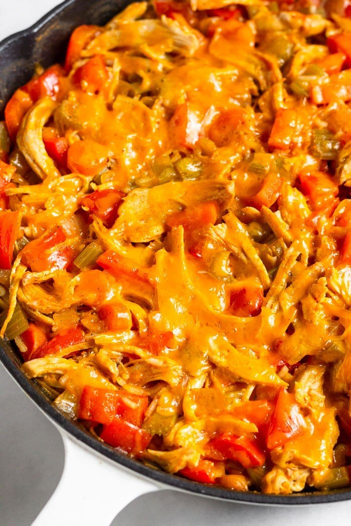 Close up of a pan of healthy buffalo chicken and rice casserole topped with cheese.