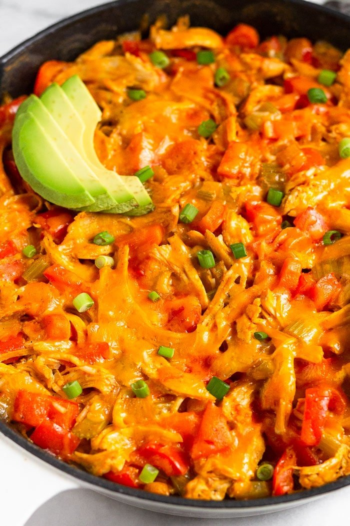 Close up a buffalo chicken casserole with melted cheese topped with avocado and green onion.