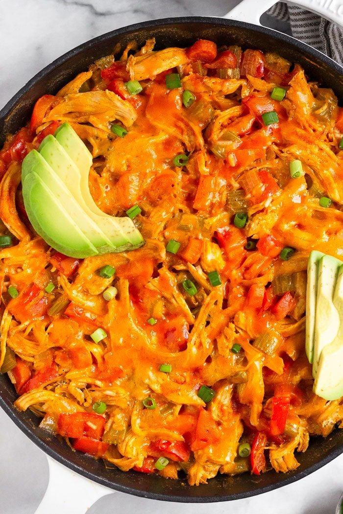 Buffalo chicken and rice casserole in a large cast iron topped with melted cheese, avocado, and green onion.